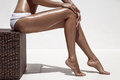 Beautiful woman tan legs. Against white wall. Royalty Free Stock Photo