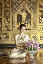 A beautiful woman in Thai national costume during the Ayuthaya period was sitting on a string of garlands. And smile beautifully Royalty Free Stock Photo