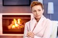 Beautiful woman thinking by fireplace Royalty Free Stock Photo