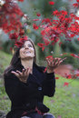 Beautiful woman throwing autumn red leaves Royalty Free Stock Photo