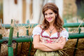 Beautiful woman in traditional bavarian dress against hay wagon Royalty Free Stock Photo