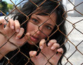 Beautiful woman trapped behind a fence. Stock Image
