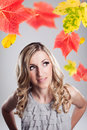 Beautiful woman under autumn leaves young with lovely curly blond hair standing colourful red and yellow looking up at them with a Stock Images
