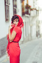 Beautiful woman in urban background vintage style portrait of a pretty wearing a red dress Stock Photography