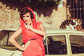 Beautiful woman in urban background vintage style portrait of a pretty wearing a red dress with a old car and a cat Stock Photo