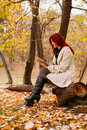 Beautiful woman using digital tablet in park young female sitting on tree and smiling looking into forest with pc her hand autumn Royalty Free Stock Photo