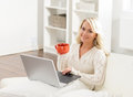 Beautiful woman using laptop and having a cup of coffee in the morning Royalty Free Stock Photo