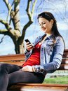 Beautiful woman using smartphone on park bench photo of a young a while sitting in a a Royalty Free Stock Images