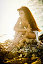Beautiful woman with long hair in bathing suit sitting on the beach in summer day. Portrait of a slim redhead in bikini on beach