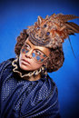 Beautiful woman in venetian mask with feathers and jewelry a suit of blue color on a blue background Royalty Free Stock Images