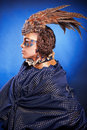 Beautiful woman in venetian mask with feathers and jewelry a suit of blue color on a blue background Stock Photography