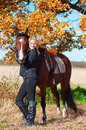 Beautiful woman walking with horse and oak tree as background Stock Photos