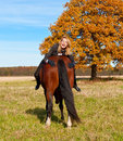Beautiful woman walking with horse smiling and holding butt Stock Image