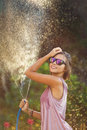 Beautiful woman watering roses with a garden hose Royalty Free Stock Photo