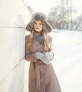 Beautiful woman wearing a coat jacket and hat over snow in winter Royalty Free Stock Photo