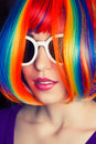 Beautiful woman wearing colorful wig and white sunglasses agains Royalty Free Stock Photo
