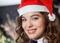 Beautiful woman wearing santa hat in christmas closeup portrait of young store Royalty Free Stock Photo