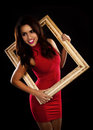 A beautiful woman wearing a sexy red dress and holding a antique picture frame on a black background Royalty Free Stock Image