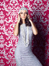 Beautiful woman wearing silver dress and hat posing on ornamentall background Royalty Free Stock Photo