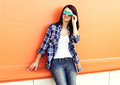 Beautiful woman wearing a sunglasses and checkered shirt over colorful orange Royalty Free Stock Photo