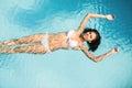 Beautiful woman in white bikini floating in swimming pool Royalty Free Stock Photo