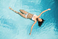 Beautiful woman in white bikini floating in swimming pool Royalty Free Stock Photo