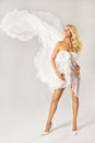 Beautiful woman in white dress with flying dynamic fabric blonde Stock Photos