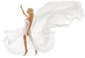 Beautiful woman in white dress with flying fabric blonde walking over isolated background Stock Image