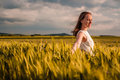 Beautiful woman in white dress on golden yellow wheat field Royalty Free Stock Photo