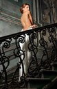 Beautiful woman in white dress with naked back in palace portrait of the she is going upstairs studio interior of old not Stock Images