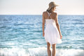 Beautiful woman in a white dress walking on the beach.Relaxed woman breathing fresh air,emotional sensual woman near the sea, enjo Royalty Free Stock Photo