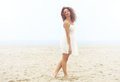 Beautiful woman in white dress walking on sand at the beach portrait of a Royalty Free Stock Photography