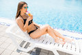 Beautiful woman in white summer dress laying with cocktail on lounge chair at poolside. Summer time Royalty Free Stock Photo
