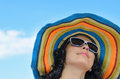 Beautiful woman in a wide brimmed low angle portrait of colourful striped straw sunhat against blue sky Stock Photography