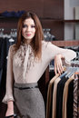 Beautiful woman and wide choice of clothes Royalty Free Stock Images