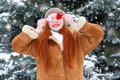 Beautiful woman on winter outdoor posing with heart shape toys, holiday concept, snowy fir trees in forest, long red hair, wearing Royalty Free Stock Photo