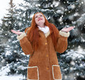 Beautiful woman on winter outdoor, snowy fir trees in forest, long red hair, wearing a sheepskin coat Royalty Free Stock Photo