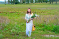 Beautiful woman wiyh bunch of flowers young hippie on the grassland Royalty Free Stock Images