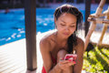 Beautiful woman working on her communications poolside on holiday Royalty Free Stock Photo