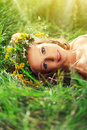 Beautiful woman in wreath of flowers lies in the green grass out young outdoors nature Royalty Free Stock Photography