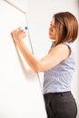 Beautiful woman writing on a board Royalty Free Stock Photo