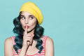 Beautiful woman in a yellow beret makes a gesture of silence. Royalty Free Stock Photo