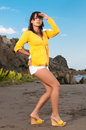 Beautiful woman in yellow looking for somebody the beach Stock Image