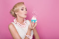 Beautiful women with cream dress holding small cake with colorful candle. Birthday, holiday