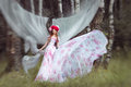 Beautiful women in developing the wind long dress woman a mysterious forest Royalty Free Stock Photo