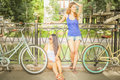 Beautiful women dressed in shorts resting after travel by bicycle Royalty Free Stock Photo