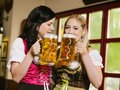 Beautiful women drinking oktoberfest beer photo of two wearing traditional dirndl and Royalty Free Stock Photography