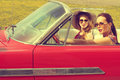 Beautiful women driving a red car retro vintage wearing accesoriess Royalty Free Stock Photo