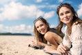 Beautiful women lying on beach laughing looking away Royalty Free Stock Photo