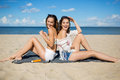 Beautiful women relaxing on beach laughing Royalty Free Stock Photo